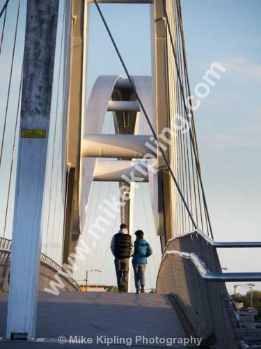 Couple Walking over the Infiniti Bridge over the River Tees between Stockton and Thornaby, Cleveland. - Cleveland, Stockton on Tees, Infiniti, Bridge, River, Tees, dual, tied arch bridge, bowstring bridge, Engineering, Couple, Walking,
