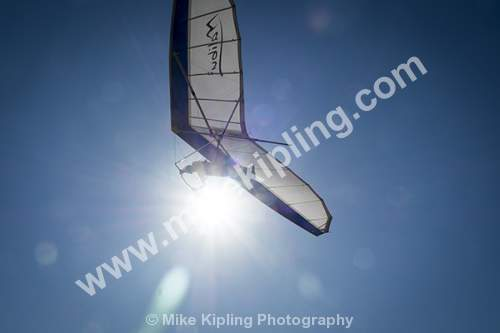 Close up of Hang Glider against the Sun and Blue Sky - Australia, Coast, Hang, Glider, Pilot, Flying, Arial,